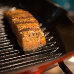 A photo of salmon being grilled on a Le Creuset griddle pan